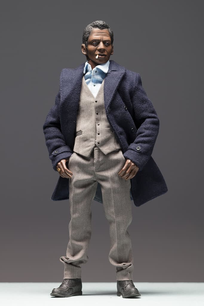 8 inch figurine of James Baldwin wearing a blue coat, hands in pockets and smoking a cigarette.