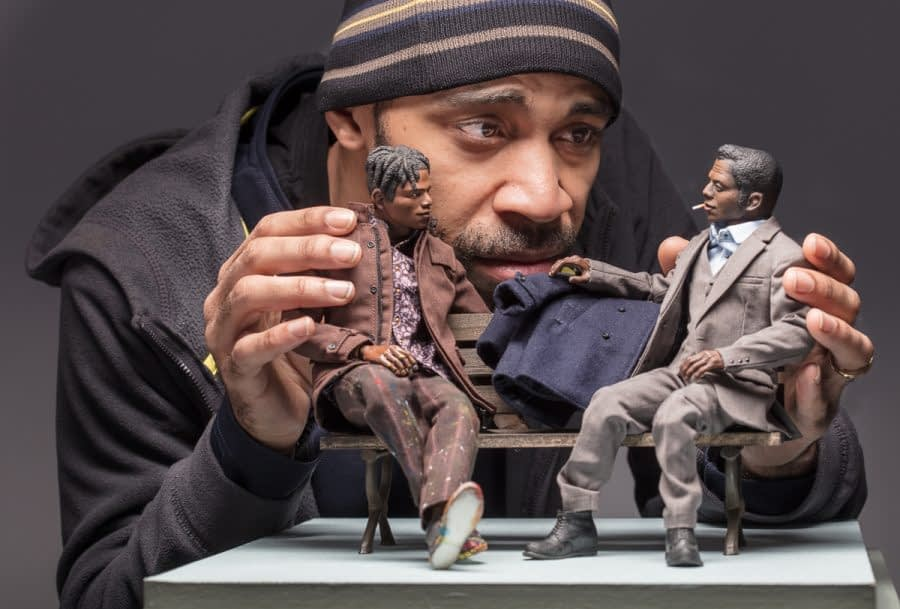 Artist Acori Honzo holds two 8-inch tall dolls of James Baldwin and Jean Michel Basquiat. Acori's face is at the level of the dolls and accentuates their small and beautifully detailed proportions.