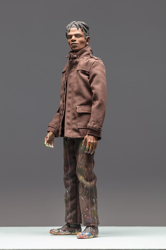 8-inch figurine of artist Jean-Michel Basquiat. He has a contemplative expression and is wearing a brown coat with his collar pulled up around his face.